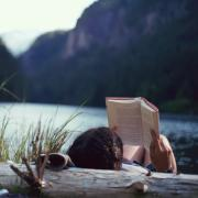 girl reading book by the water