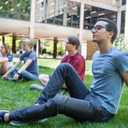 Students sit in the grass outside the engineering building, listening to a lecture