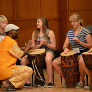 Students in a Summer Music Academy camp play drums with their instructor.