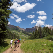 People hiking on a scenic trail in the mountains.