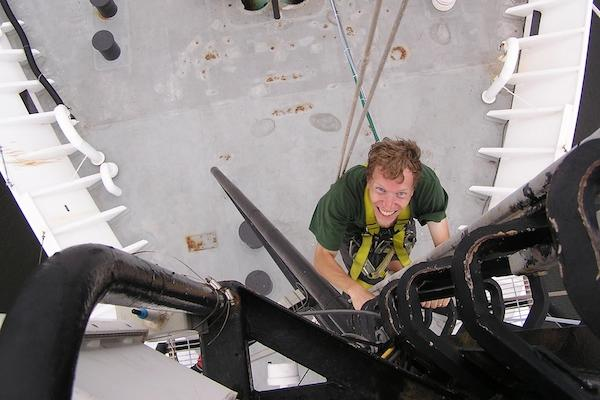 Researcher climbing up a ship out on the ocean.