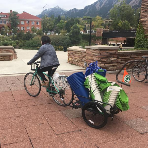 A member of the Green Team using a bike to transport waste baskets on campus.