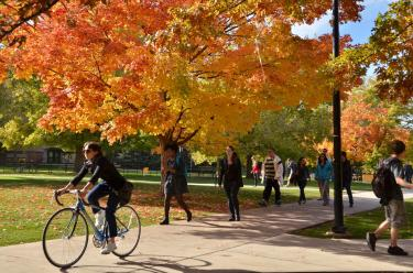 Person riding a bike across Norlin Quad in fall.