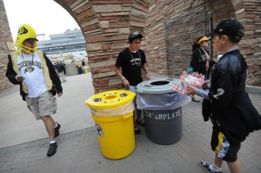 Alex Mitoma, a CU-Boulder environmental engineering student, center, volunteers to show football fans which bin to put their waste away during the CU vs. Hawaii football game at Folsom Field on Sept. 18, 2010.