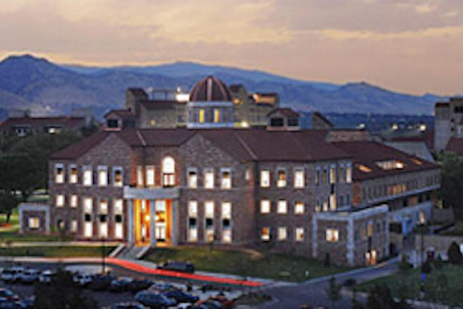 Campus building at dusk with lights on