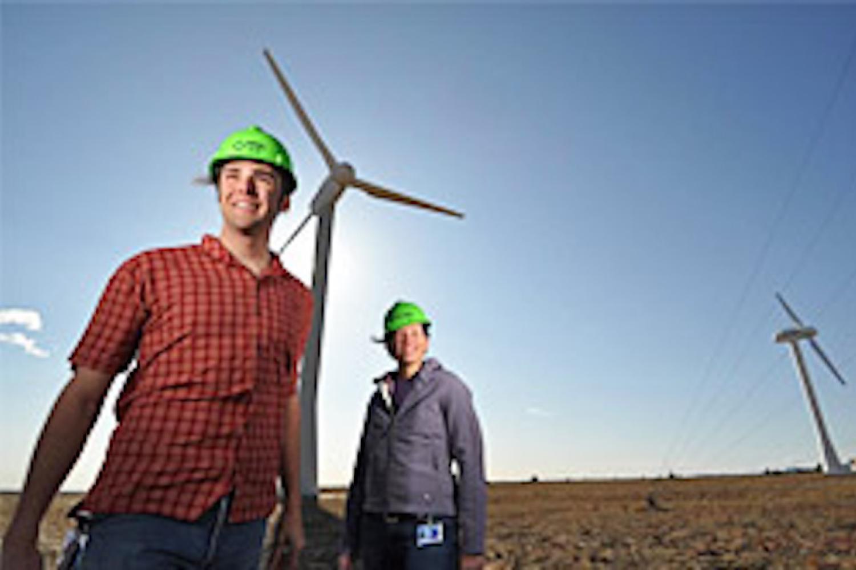 Workers in hard hats under Wind turbine