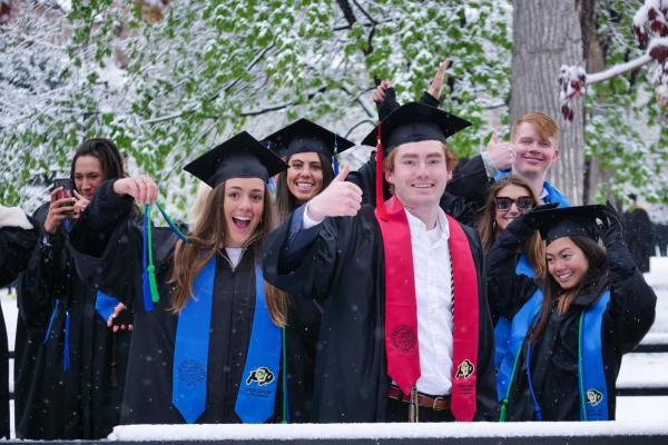 graduating students give thumbs up at commencement