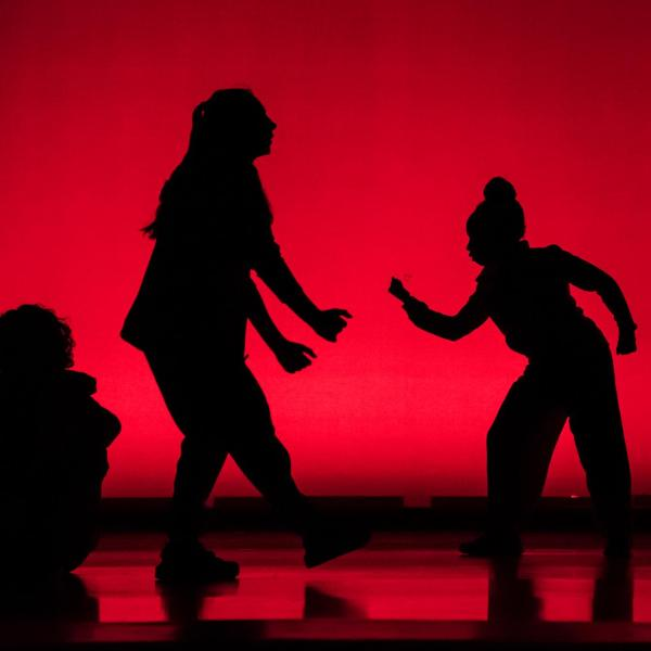 Dance performance in a red lit theatre