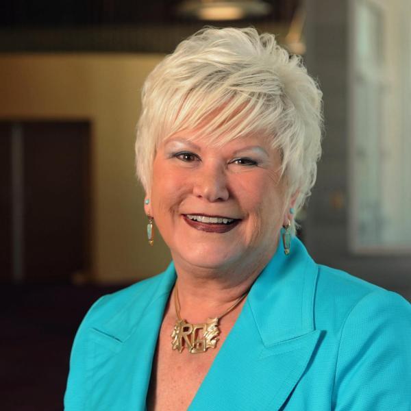 woman facing front smiling blond, short hair