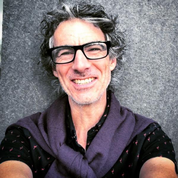 Man with medium length salt and pepper hair wearing black frame glasses