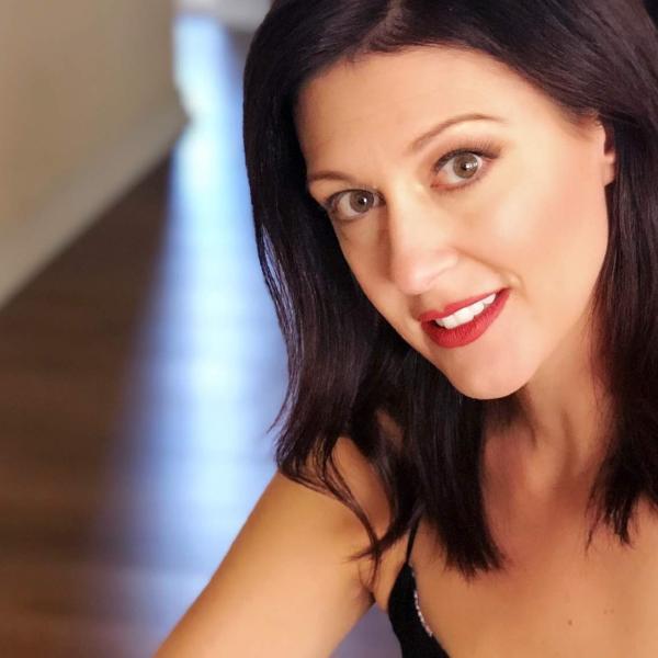 woman facing front smiling, short hair
