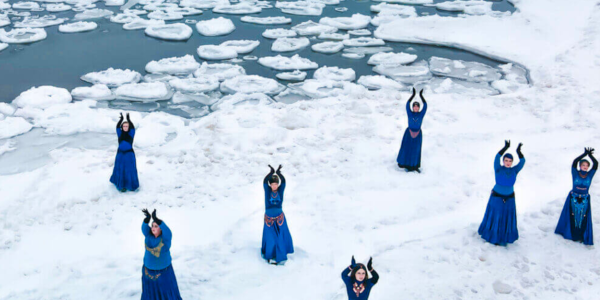 dancers in blue perform on snow and ice