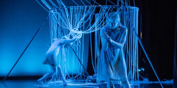 Students performing a dance composition in a blue lit theatre