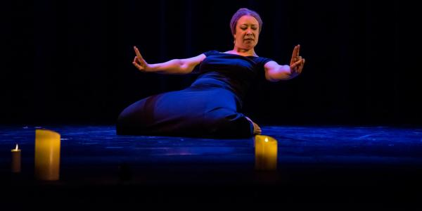 Faculty member dancing in a candle lit theatre