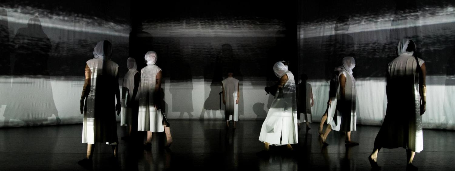 Several dancers walking on stage. Each wears a face covering. The backdrop is white and black stripes