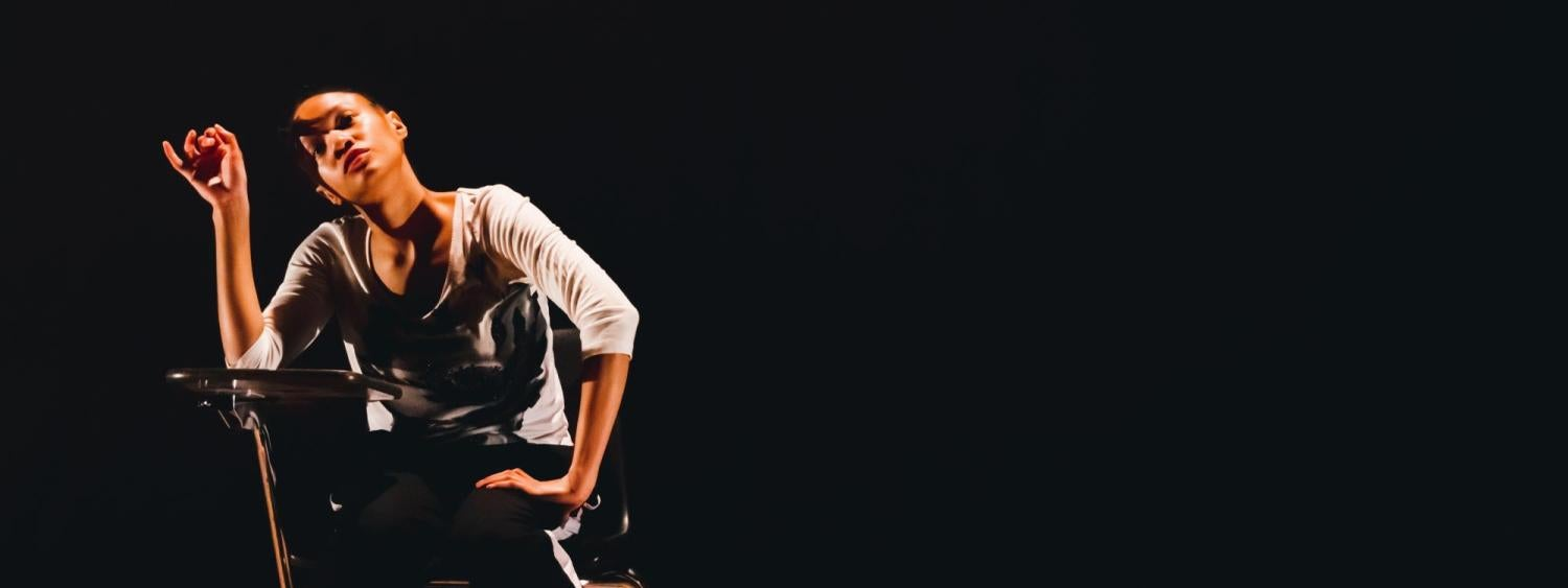 A dancer sits at a desk, alone on stage