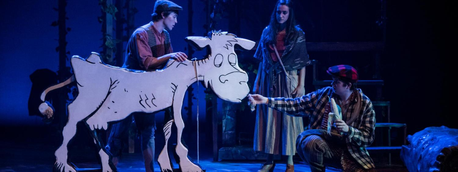 An actors feeds corn to a wooden cow