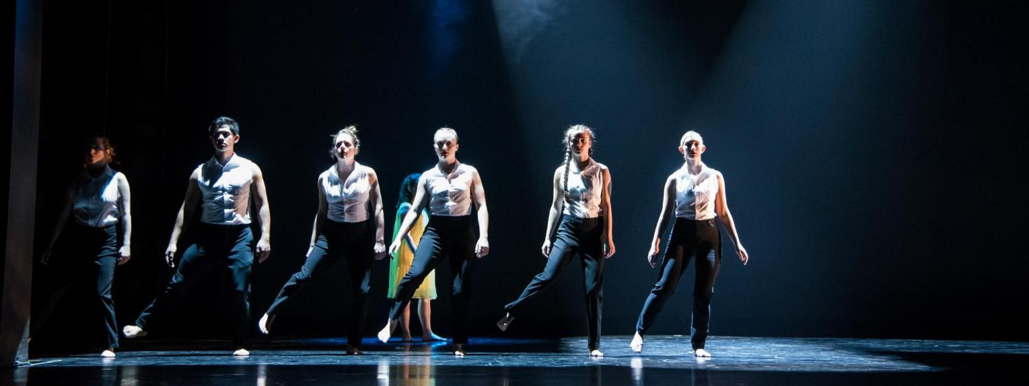 Six dancers stand in a row downstage in hazy light