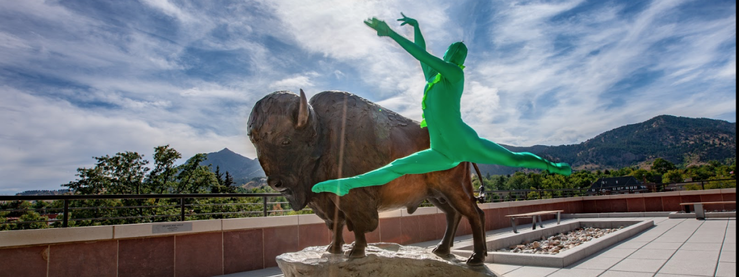 Person wearing a green suit leaping in front of a statue of Ralphie