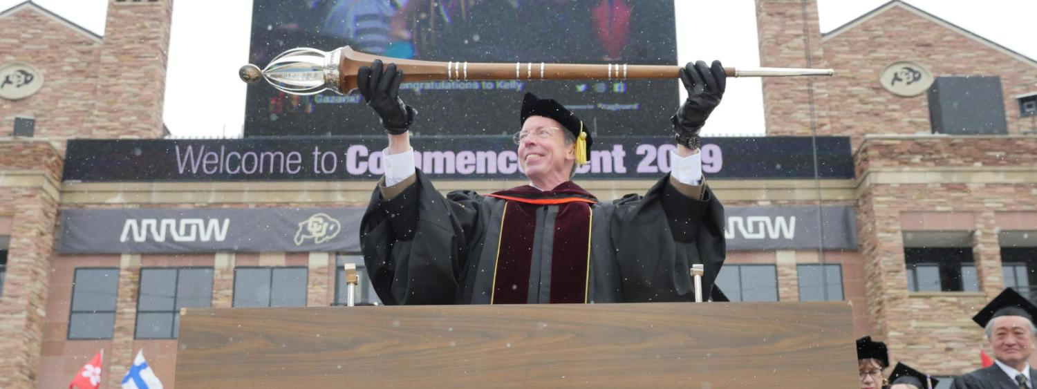A faculty member lowers a Mace during the 2019 Commencement Ceremony
