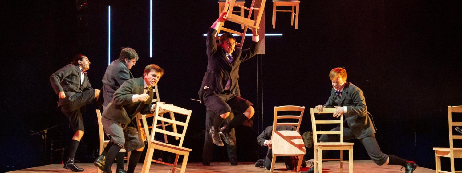 Student performers stamp around on stage and throw chairs