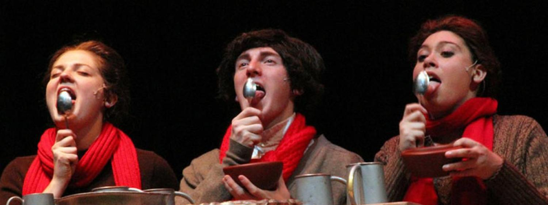 three students lick spoons
