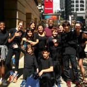 Cast of 8 students facing front outside the Goodman Theatre in NY