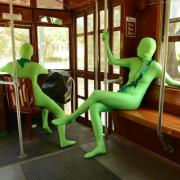 People in green suits sitting on trolley