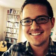 man wearing black rimmed glasses smiling