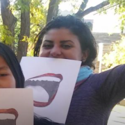 Fahmy holding paper sign with open mouth on it in front of her face