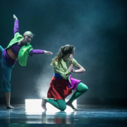 Dancers in bright purple, green, blue and red costumes under lighting