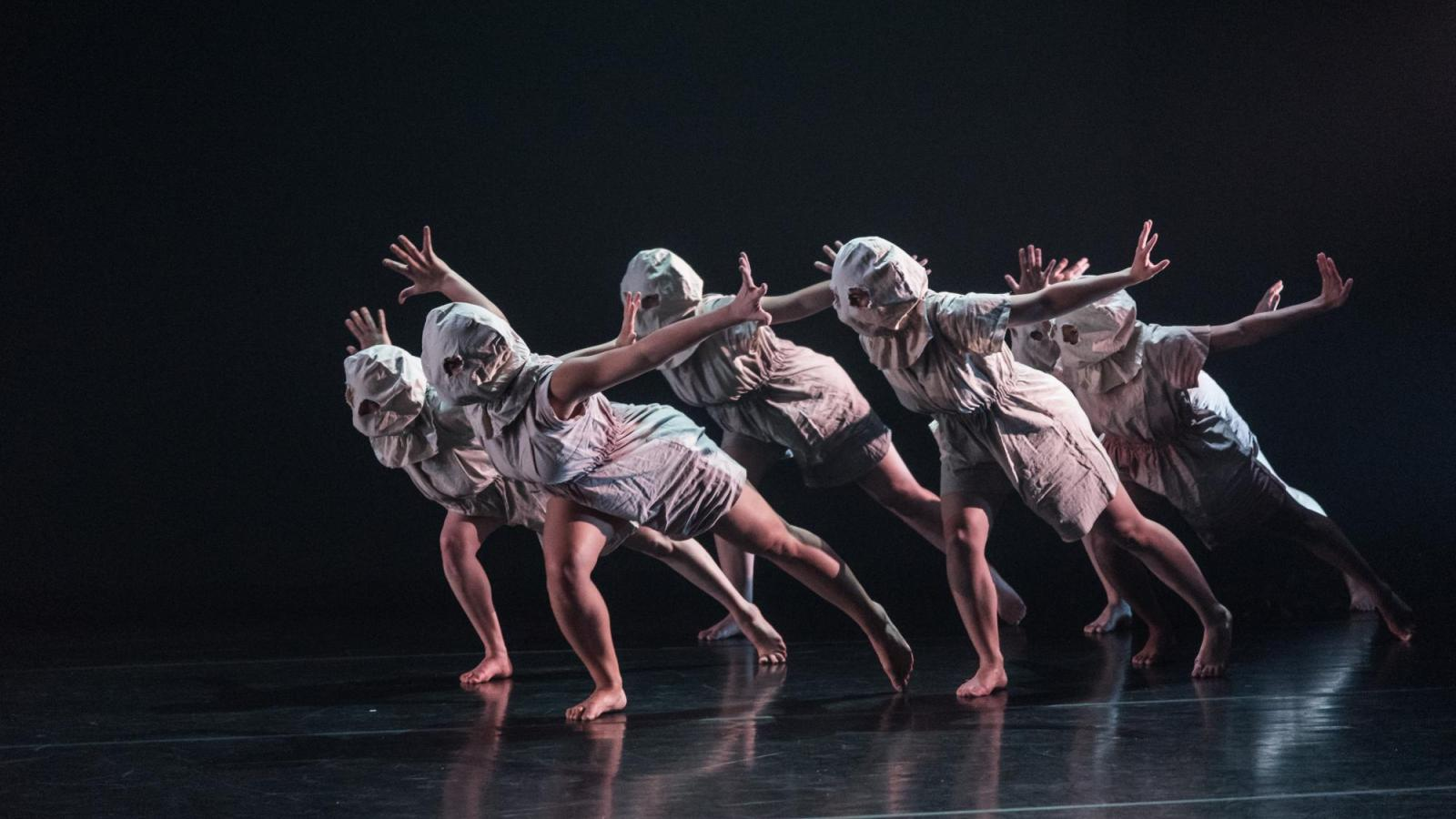 Five masked dancers move onto the stage