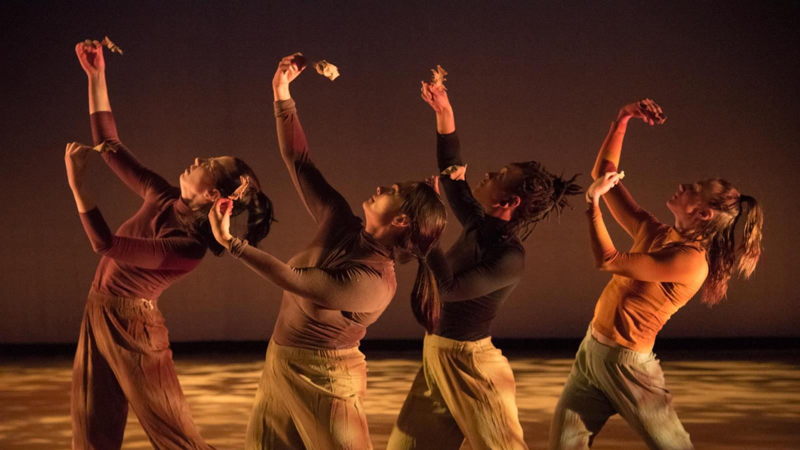 Four dancers hold up leaves