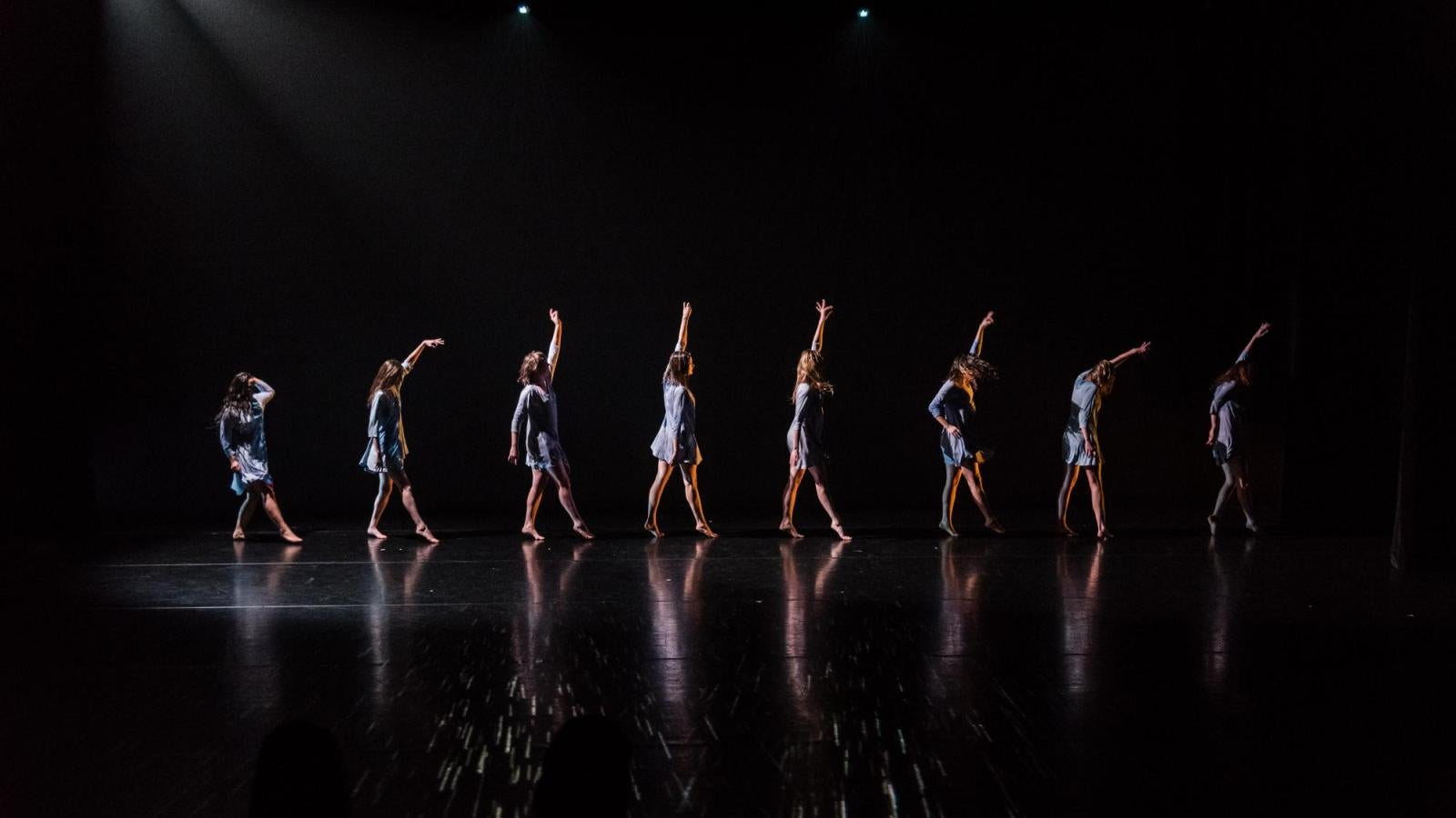 Eight dancers in a line on stage