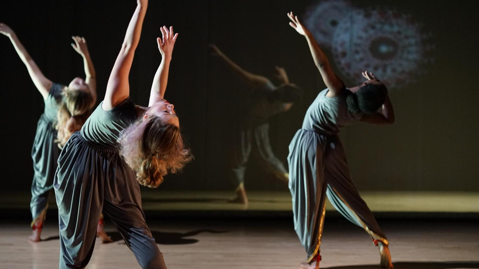 dancers on stage, leaning back while reaching up to the ceiling
