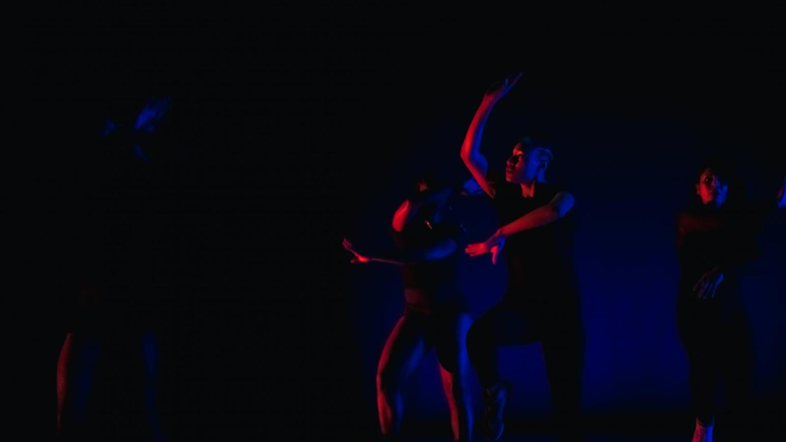 Several dancers perform on a darkly lit stage with red and blue lighting
