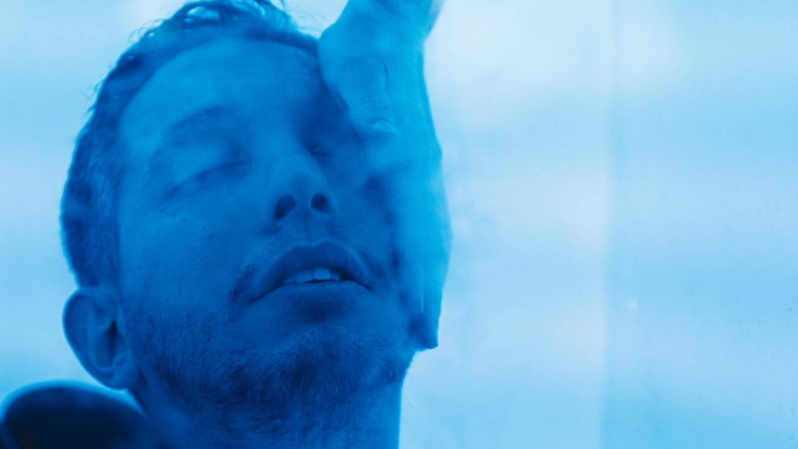 A person touches a man's face, and the man is shrouded in a blue haze