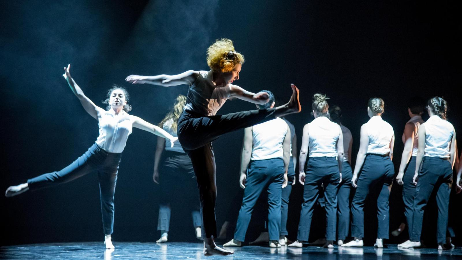 Two students dance downstage while several others stand upstage in a line