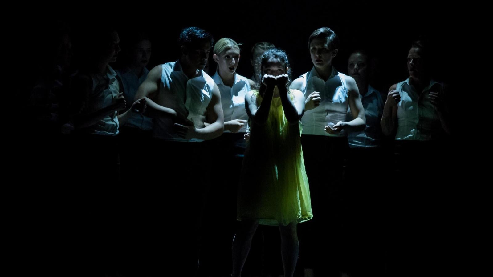 One dancer in yellow clenches her fists while several others surround her in business attire