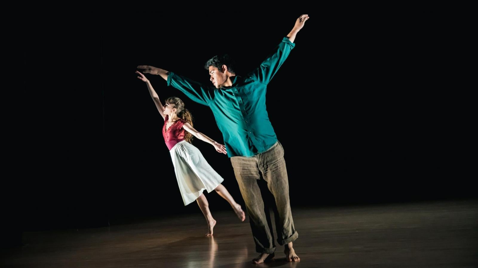One male dancer leans to the left while a female dancer moves behind him