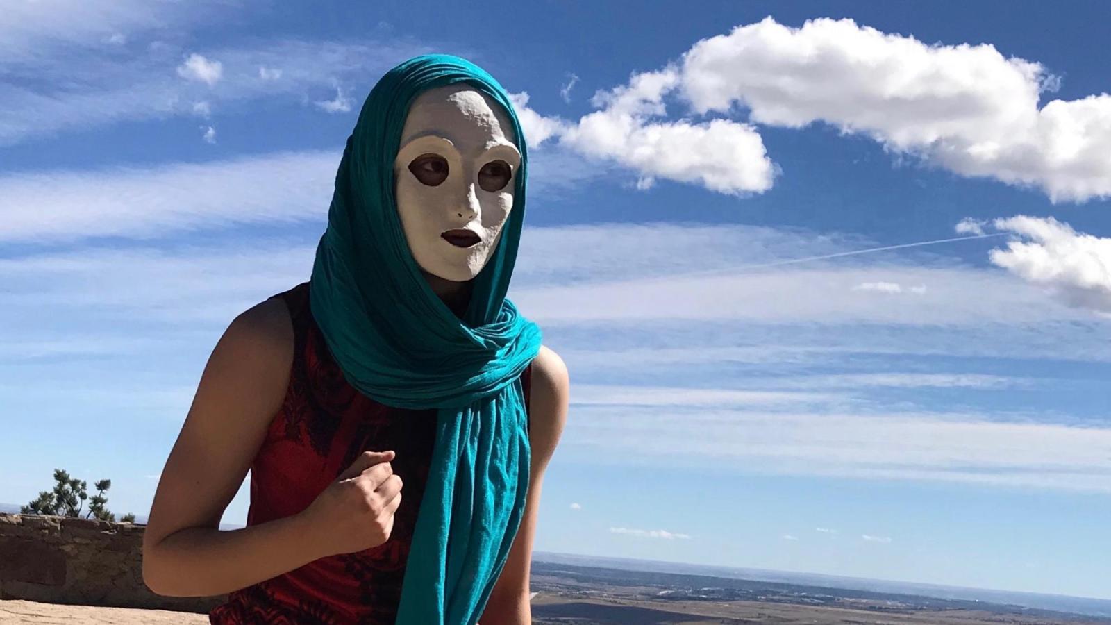 A masked performer runs on a mountaintop