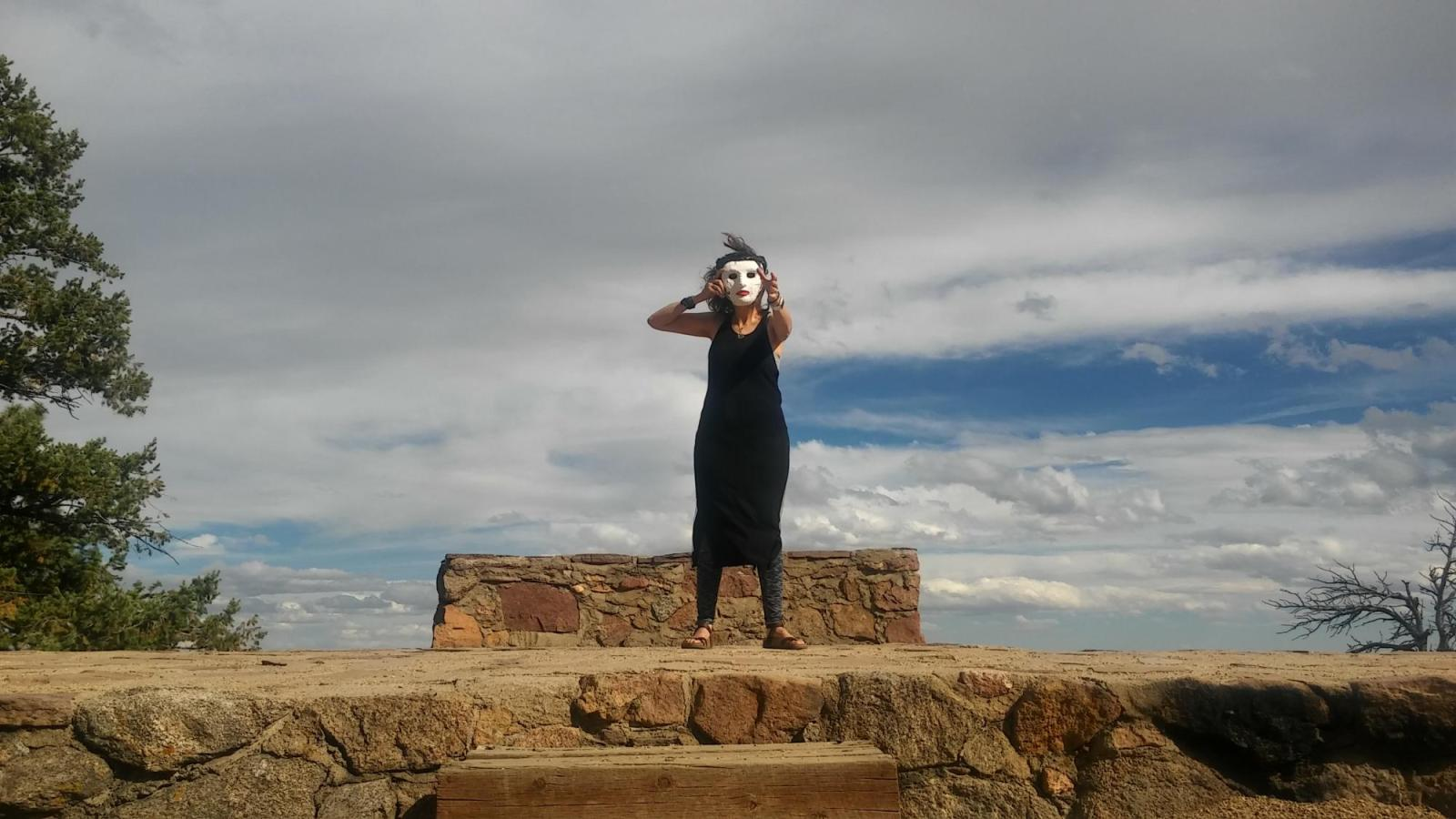 A masked performer reaches out from the top of a stone landing