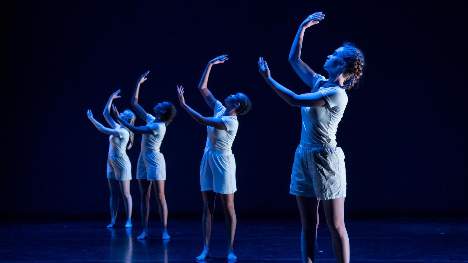 Four dancers in a line with their arms up