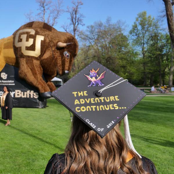 Female in grad cap and CU Buffalo in the background