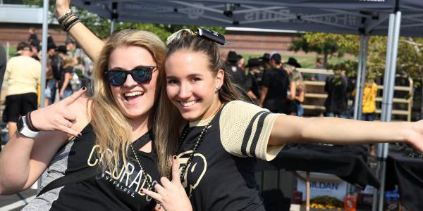 Two students in CU gear on the quad