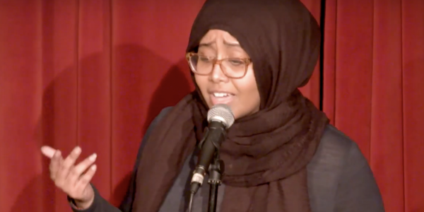 Woman in a hijab speaking in front of a mic