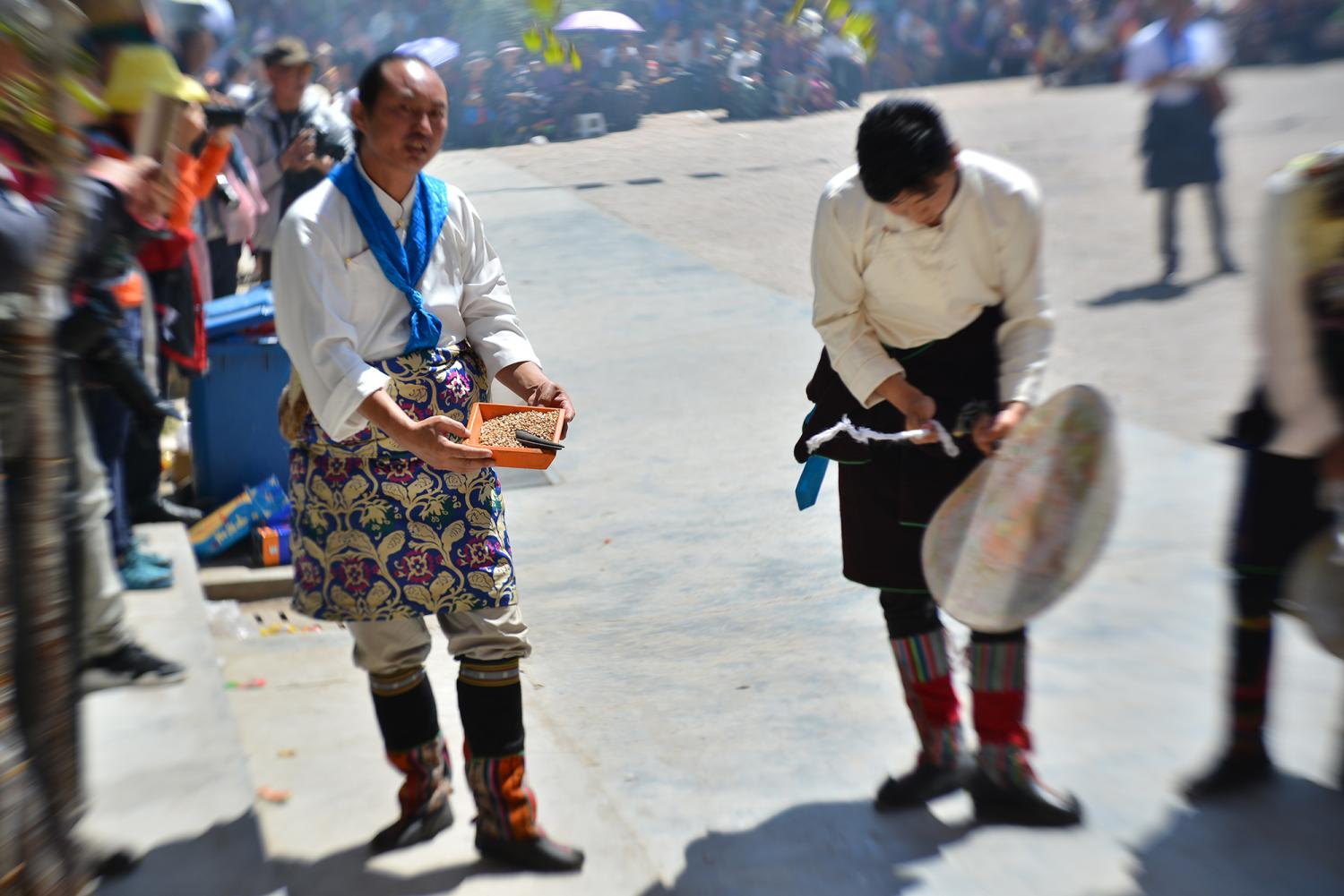 The La ba is pictured at left, holding a box of grain. He will shout and sputter his lips for the entire day as he carries out a number of ritual activities.