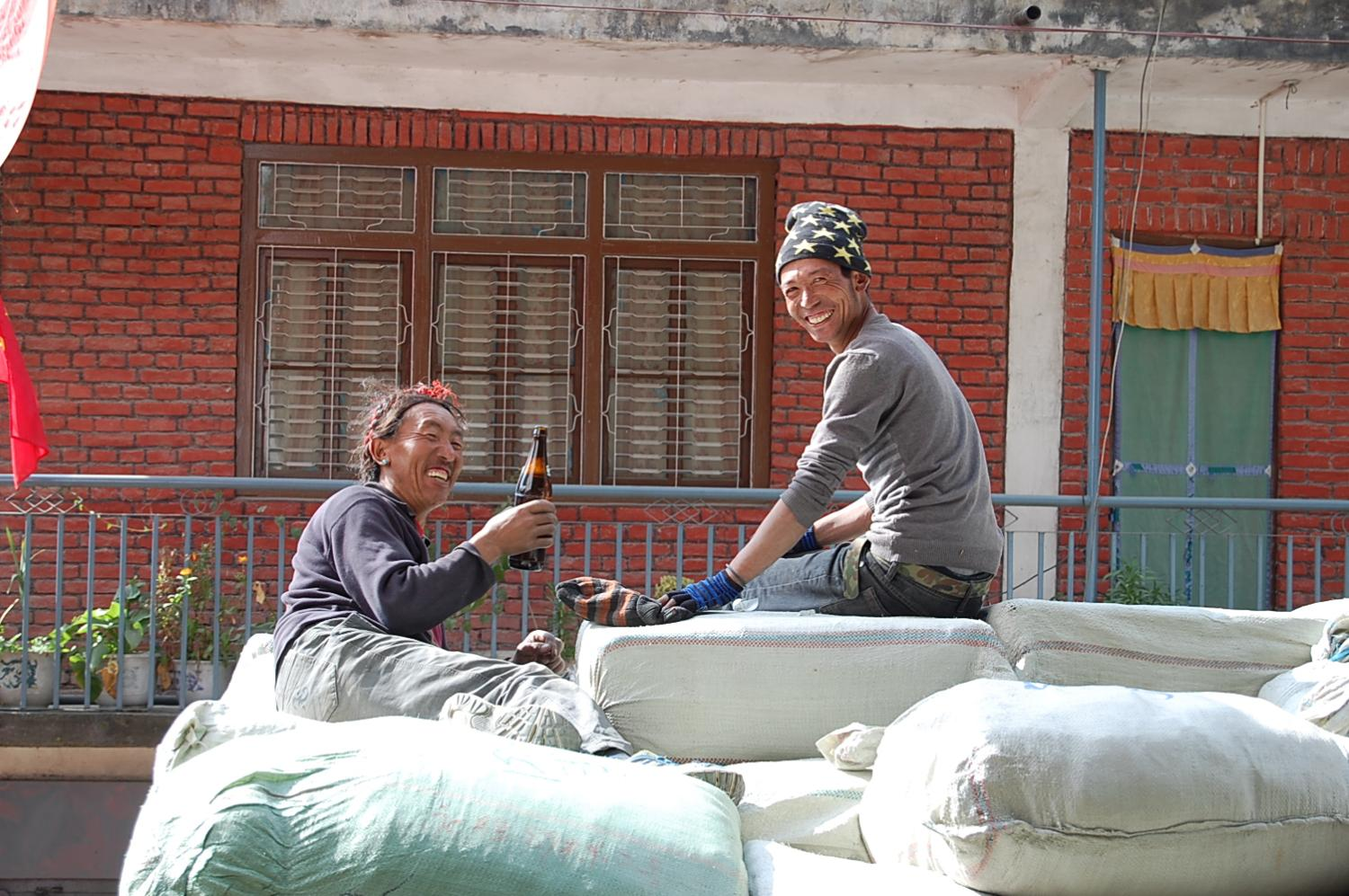 Tibetan stevedores from Tingri taking a beer break at Zhangmu while unloading Chinese garments for export to Nepal