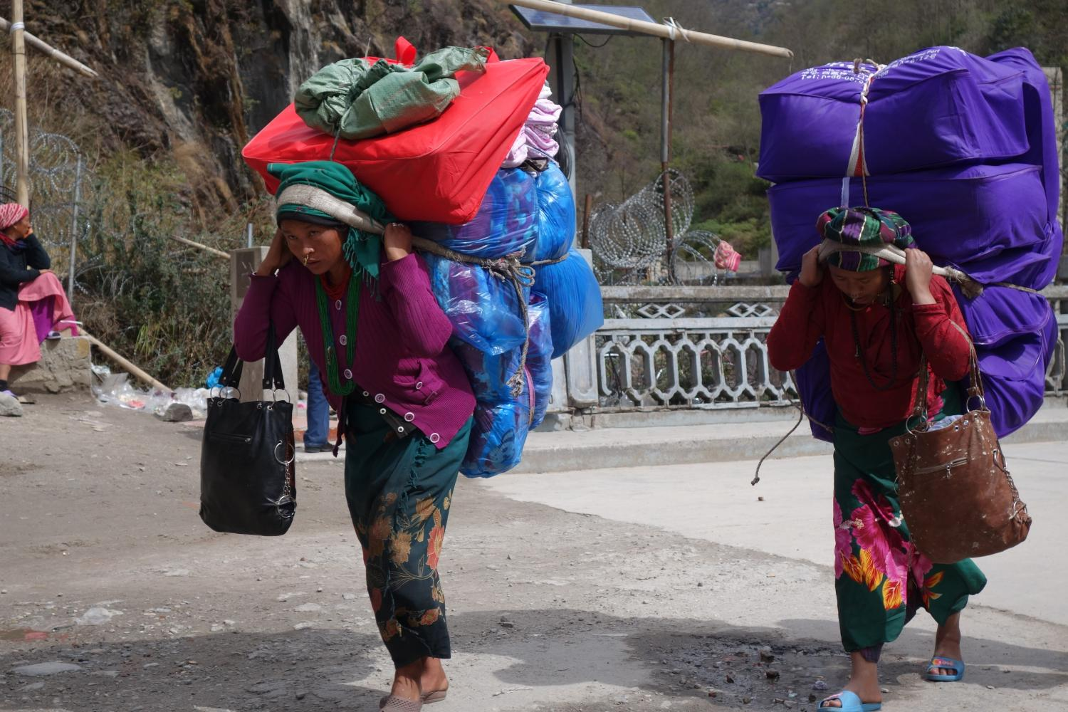 "Portering Chinese goods from Zhangmu to Kodari, these local Tamang and Rai women get the most out of the daily allowance of one person-load of imports for Nepal-Tibet ""border citizens"""
