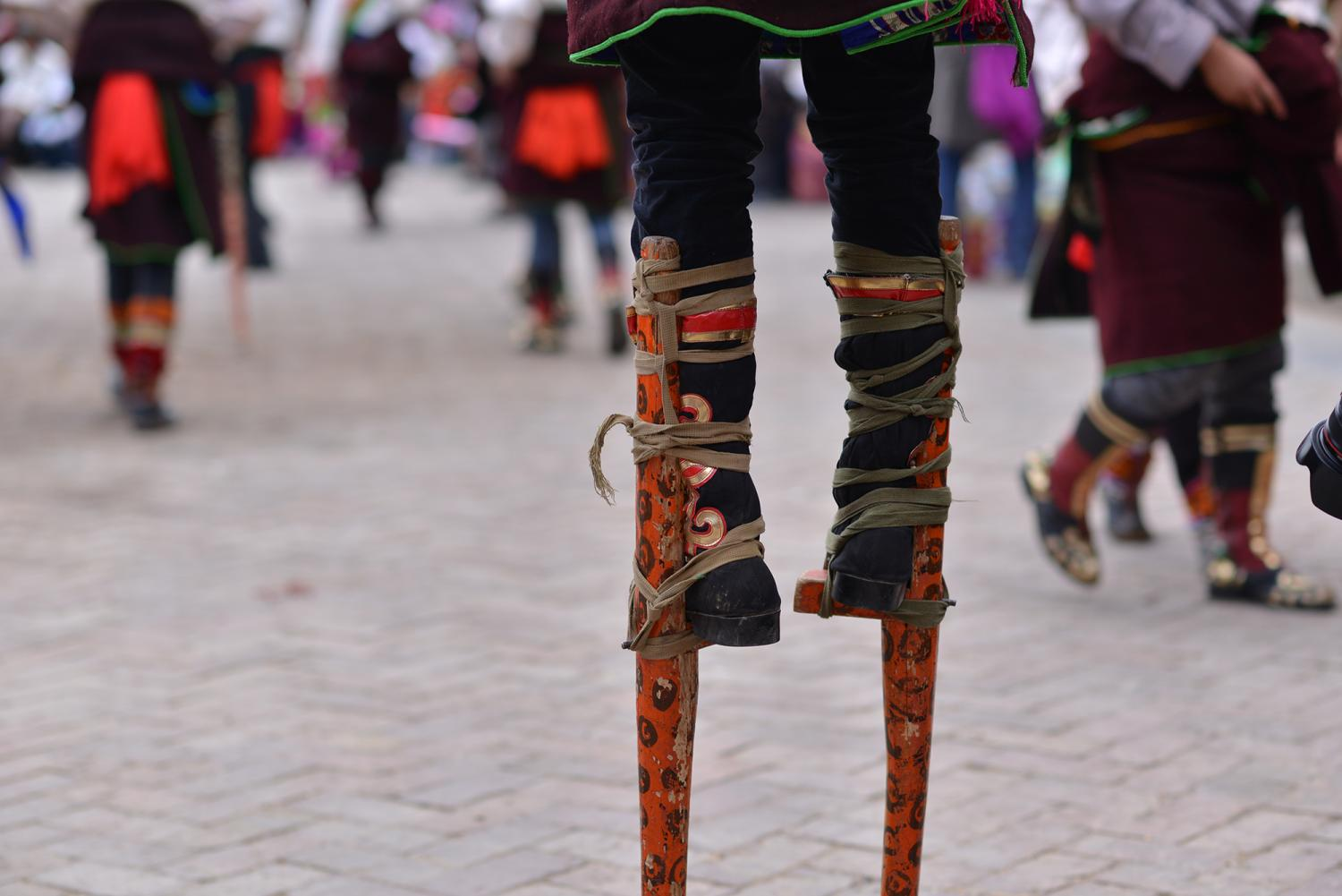 """A young man wears stilts as he dances around the courtyard on stilts or """"wooden feet"""" called Kang hung (Rkang shing, རྐང་ཤིང་)."""